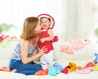 Happy  Mother and baby girl with clothes ready for traveling on. Happy Mother and baby girl with clothes ready for traveling on vacation Royalty Free Stock Images