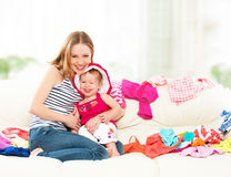Happy  Mother and baby girl with clothes ready for traveling on. Happy Mother and baby girl with clothes ready for traveling on vacation Royalty Free Stock Photography