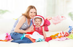Happy  Mother and baby girl with clothes ready for traveling on. Happy Mother and baby girl with clothes ready for traveling on vacation Royalty Free Stock Photo