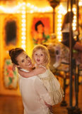 Happy mother and baby girl in front of carousel Royalty Free Stock Images