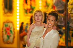 Happy mother and baby girl in front of carousel Royalty Free Stock Photos