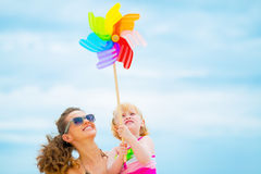 Happy mother and baby girl holding windmill. Happy mother and baby girl holding colorful windmill toy Royalty Free Stock Photo