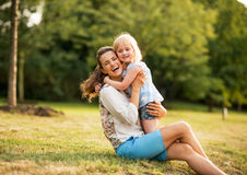 Happy mother and baby girl hugging in park Stock Photos