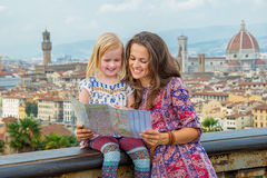 Happy mother and baby girl looking at map in florence, italy Royalty Free Stock Photos