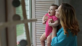 Happy mother with baby girl looking through window stock footage