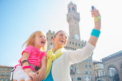 Happy mother and baby girl making selfie in florence, italy