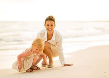 Happy mother and baby girl playing on the beach Stock Photos