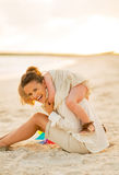 Happy mother and baby girl playing on the beach Stock Photography