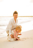 Happy mother and baby girl playing on the beach Royalty Free Stock Photos