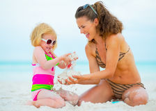 Happy mother and baby girl playing on beach Royalty Free Stock Images