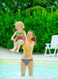 Happy mother and baby girl playing in pool Royalty Free Stock Images