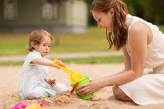 Happy mother with baby girl playing in sandbox Royalty Free Stock Images