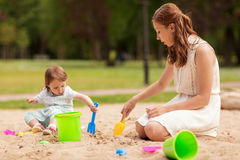 Happy mother and baby girl playing in sandbox Stock Images