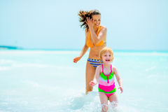 Happy mother and baby girl playing on sea shore Royalty Free Stock Images