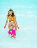 Happy mother and baby girl playing in sea Stock Photo