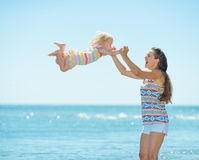 Happy mother and baby girl playing at seaside Royalty Free Stock Images