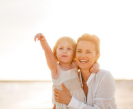Happy mother and baby girl pointing on copy space Stock Photos