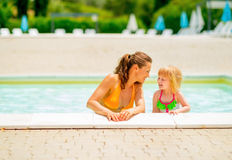 Happy mother and baby girl at poolside Royalty Free Stock Photos