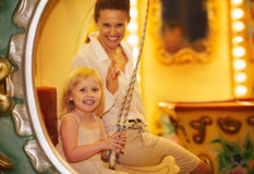 Happy mother and baby girl riding on carousel Royalty Free Stock Photos