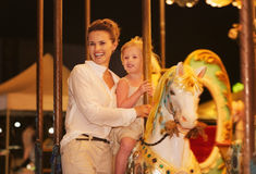 Happy mother and baby girl riding on carousel Stock Photo