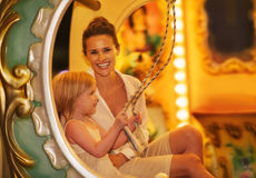 Happy mother and baby girl riding on carousel Royalty Free Stock Images