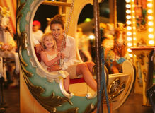 Happy mother and baby girl riding on carousel Stock Photos