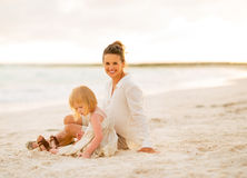 Happy mother and baby girl sitting on the beach. In the evening Stock Photos