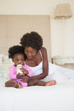 Happy mother and baby girl sitting on bed together Royalty Free Stock Photography