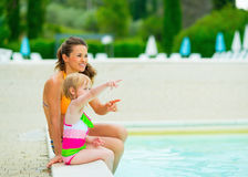 Happy mother and baby girl sitting near pool Stock Image