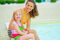 Happy mother and baby girl sitting at poolside Royalty Free Stock Image