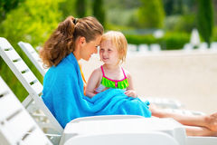 Happy mother and baby girl sitting on sunbed Stock Photos