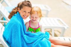 Happy mother and baby girl on sunbed. Portrait of happy mother and baby girl wrapped in towel sitting on sunbed Stock Photo
