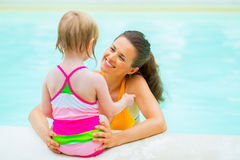 Happy mother and baby girl in swimming pool. Happy mother and baby girl in bikini in swimming pool royalty free stock photography