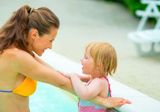 Happy mother and baby girl in swimming pool. Portrait of happy mother and baby girl in swimming pool stock photography