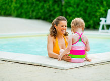 Happy mother and baby girl in swimming pool. Portrait of happy mother and baby girl in swimming pool stock photos