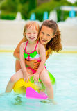 Happy mother and baby girl in swimming pool. Portrait of happy mother and baby girl sitting on ball in swimming pool royalty free stock photography