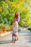 Happy mother and baby girl walking in city park Royalty Free Stock Photos