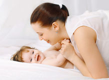 Happy mother and baby having fun in bed Stock Photo
