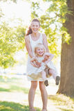 Happy mother and baby having fun outdoors Stock Photos