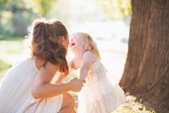 Happy mother and baby having fun in park Royalty Free Stock Images