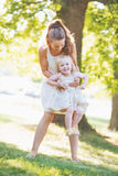 Happy mother and baby having fun in park Royalty Free Stock Photo