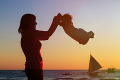 Happy mother and baby having fun at sunset beach Stock Images