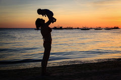 Happy mother and baby having fun at sunset beach Stock Photography