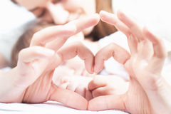 Happy mother and baby. Heart symbol by hands. Family care stock photo