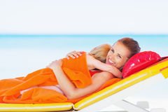 Happy mother and baby laying on chaise-longue. Happy young mother and baby laying on chaise-longue on beach Royalty Free Stock Photography