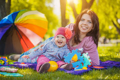Happy mother and baby are laying on meadow Stock Images