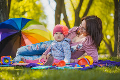 Happy mother and baby are laying on meadow Stock Photo