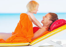 Happy mother and baby laying on sunbed. Happy young  mother and baby girl laying on sunbed on beach Royalty Free Stock Photos