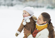 Happy mother and baby looking on copy space in winter outdoors Stock Image