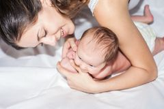 Happy mother with a baby lying on a white bed Royalty Free Stock Image